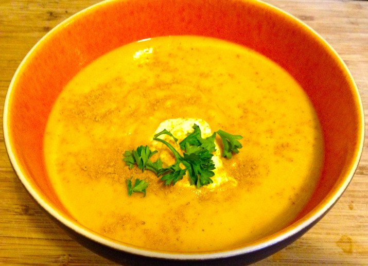 Butternut Squash Soup Topped with Vegan Sour Cream and a Sprig of Parsley